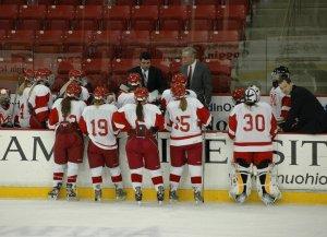 Coach Scott Hicks (center, dark suit) leads the Lady RedHawks.